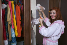 Woman cleaning furniture cabinet Stock Photography