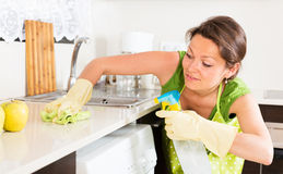 Woman cleaning furniture in kitchen Stock Photo