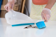 Woman cleaning garbage from white table with Brush and Shovel Royalty Free Stock Photos