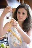 Woman cleaning glassware. A view of a young woman with a drying towel, checking a large beverage glass to make sure it is clean and dry Royalty Free Stock Images
