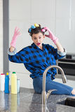 Woman IN a cleaning gloves sitting on a kitchen worktop Royalty Free Stock Photo
