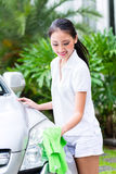 Woman cleaning headlamp at car wash Stock Images