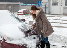 Woman cleaning her car after snow blizzard Stock Image