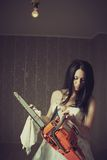 Woman cleaning her chainsaw. Pretty bride cleaning her bloody chainsaw royalty free stock photography