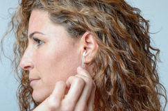 Woman cleaning her ear with a cotton swab. Side view Close up of the face of an middle aged woman cleaning her ear with a cotton swab royalty free stock images