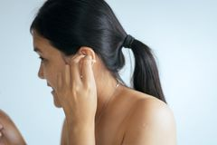 Woman cleaning her ears with cotton bud in bedroom,Female using cotton stick stock photo