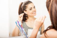 Woman cleaning her ears with cotton swabs. Beautiful young woman using a cotton swab to clean her ears while standing in front of a mirror in a bathroom stock photo