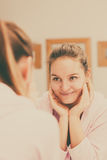 Woman cleaning her face with scrub in bathroom. Stock Photo