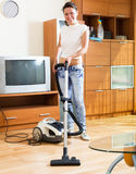 Woman cleaning her room with vacuum cleaner Stock Photography