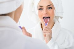 Woman cleaning her tongue Stock Photo