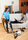 Woman cleaning at home while man with notebook Stock Images