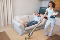 Woman cleaning house while carrying baby Royalty Free Stock Image
