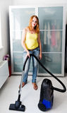 Woman cleaning the house with the Vacuum Cleaner Stock Images