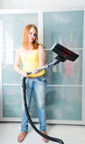 Woman cleaning the house with Vacuum Cleaner Stock Image