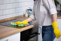 Woman cleaning induction top, hand in yellow rubber glove polish stove cooktop, closeup, no face. clear kitchen appliance. Woman cleaning induction top, hand in royalty free stock image