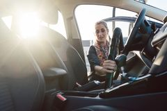 Woman cleaning inside of car. With vacuum stock photo