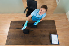 Woman Cleaning Keyboard At Desk Royalty Free Stock Image
