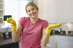 Woman Cleaning Kitchen. Young woman shrugs her shoulders while wearing dish gloves and holding a scrub pad. Horizontal shot royalty free stock images