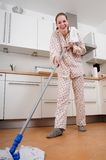 Woman cleaning the kitchen. Woman in pyjamas cleaning the kitchen stock photography
