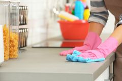 Woman cleaning kitchen counter with rag. Closeup stock image