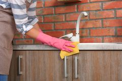 Woman cleaning kitchen counter with rag. Closeup stock photo