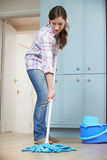 Woman Cleaning Kitchen Floor With Mop Stock Photo
