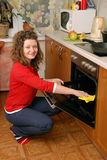 Woman cleaning kitchen oven Stock Photo