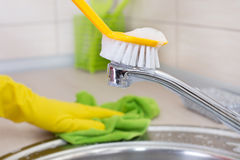 Woman cleaning kitchen sink and faucet Royalty Free Stock Image