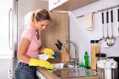 Woman Cleaning Kitchen Sink. Happy Young Woman Cleaning Kitchen Sink With Sponge And Spray In Kitchen stock photos