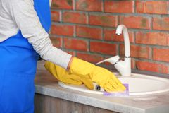 Woman cleaning kitchen sink with sponge. Closeup royalty free stock image