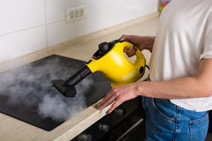 Woman cleaning kitchen with steam cleaner Stock Photography