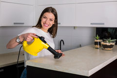 Woman cleaning kitchen with steam cleaner Stock Photo