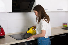 Woman cleaning kitchen with steam cleaner Stock Photos