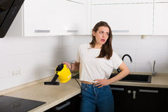 Woman cleaning kitchen with steam cleaner Royalty Free Stock Photo