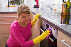 Woman cleaning the kitchen stove. Housewife cleaning the kitchen stove Stock Photography