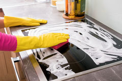 Woman cleaning kitchen stove Royalty Free Stock Image