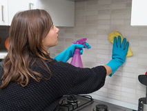 Woman cleaning kitchen tiles. At home stock photo