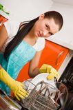 Woman cleaning kitchen using dish washing ma Royalty Free Stock Photography