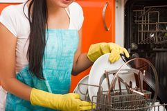 Woman cleaning kitchen using dish washing ma Stock Photos