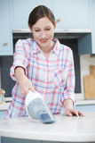 Woman Cleaning Kitchen Using Hand Held Vacuum Cleaner Stock Photography