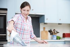 Woman Cleaning Kitchen Using Hand Held Vacuum Cleaner Royalty Free Stock Photos