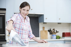 Woman Cleaning Kitchen Using Hand Held Vacuum Cleaner Stock Photo