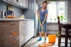 Woman cleaning in the kitchen washes the floor stock images