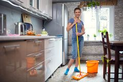 Woman cleaning in the kitchen washes the floor royalty free stock image