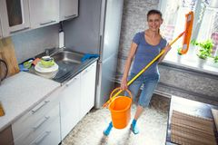 Woman cleaning in the kitchen washes the floor. At home stock photos
