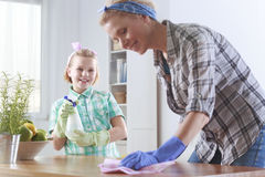 Woman cleaning in the kitchen. Young women cleaning table in the kitchen and her daughter helping her royalty free stock images