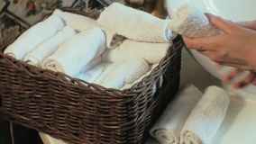 Woman folds clean soft towels in the basket, cleaning concept stock video footage