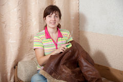 Woman cleaning leather jacket. With sponge  at home Royalty Free Stock Photos