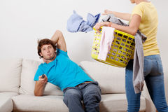 Woman cleaning man chilling Stock Photos