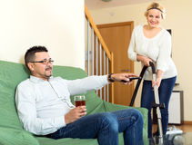 Woman cleaning while man is relaxing Royalty Free Stock Photography
